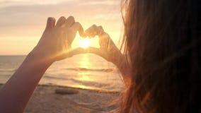 DE LANGZAME MOTIE, SLUIT OMHOOG: Onherkenbare vrouw die het plaatsen zon met haar hart gevormde vingers vangen Jong meisje die ma stock videobeelden