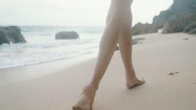 De langzame motie, sluit omhoog vrouwelijke benen lopend langs zandige strandachtergrond van oceaangolven, steadicam schot stock footage