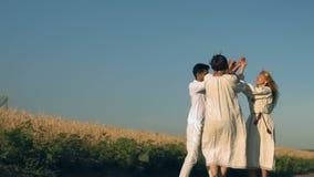 De langzame motie, twee vrouwen in nationale kostuums en een Indische man in glazen proeven op tarwegebied stock footage