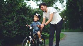 De langzame motie van gelukkige jonge mensen houdende van vader die zijn kind onderwijzen aan cyclus in groen park in de zomer, w stock video
