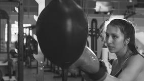 De langzame motie van jonge vrouwenbokser raakte ponsenzak tijdens pre-gelijkeopwarming met haar trainer stock footage