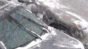 De langzame motie van mensen die sneeuw schoonmaken en het ijs van haar auto winden schildvenster stock video