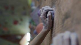 De langzame motie van rotsklimmer dient krijt in, grijpt de het beklimmen steen terwijl opleiding in het beklimmen van gymnastiek stock videobeelden