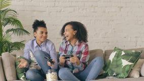 De langzame motie van twee gemengde vrienden die van het ras krullende meisje op laag zitten speelt de spelen van de consolecompu stock videobeelden