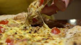 De langzame motie van Vrouw neemt een gedeelte van pizza met gesmolten kaas klaar te eten stock footage