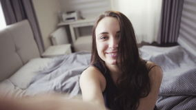 De langzame motielengte van knap vrolijk meisje gaat een ruimte in en zit op een bed, selfie schot stock footage