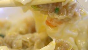 De langzame motiemensen die stokken gebruiken voor eten een bol van garnalen Aziatisch restaurant stock videobeelden