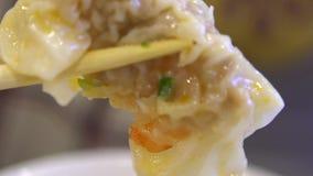 De langzame motiemensen die stokken gebruiken voor eten een bol van garnalen Aziatisch restaurant stock video