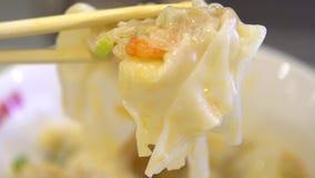 De langzame motiemensen die stokken gebruiken voor eten een bol van garnalen Aziatisch restaurant stock footage