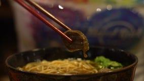 De langzame motiemensen die stokken gebruiken voor eten het traditionele restaurant van rundvleesnoedels stock footage