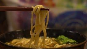 De langzame motiemensen die stokken gebruiken voor eten het traditionele restaurant van rundvleesnoedels stock videobeelden
