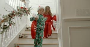 De langzame motieopeenvolging van broer en zuster die pyjama's dragen die treden reduceren die Kerstmiskous houden vulde met gift stock footage