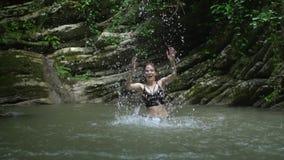 De langzame plonsen van het motie mooie meisje op water dient langs klein bergmeer dichtbij waterval in groen bos in stock videobeelden