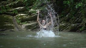 De langzame plonsen van het motie mooie meisje op water dient langs klein bergmeer dichtbij waterval in groen tropisch bos in stock video