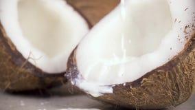 De langzame van de motiekokosmelk en kokosnoot helften stock videobeelden