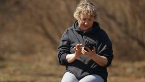 De langzame zitting van de motievrouw in het park gebruikt een slimme telefoon en is verrast stock videobeelden
