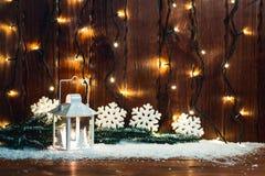 De lantaarn en de Kerstboom de takken van de Kerstmiskaars, de sneeuw, de sneeuwvlok en de decoratie op bokehachtergrond vertroeb Royalty-vrije Stock Foto's