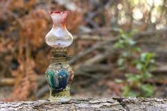 De lantaarn van de glasolie bij houten login het bos Royalty-vrije Stock Foto
