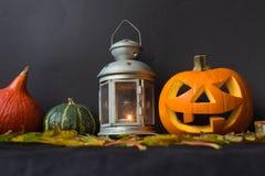 De Lantaarn van Halloween Jack o, onder de herfstbladeren, lampen en kaarsen Stock Foto