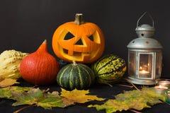 De Lantaarn van Halloween Jack o, onder de herfstbladeren, lampen en kaarsen Stock Foto's