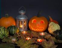De Lantaarn van Halloween Jack o, onder de herfstbladeren, lampen en kaarsen Royalty-vrije Stock Afbeeldingen
