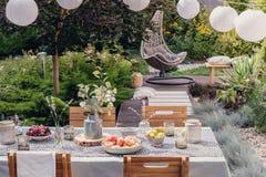 De lantaarns boven lijst met bloemen, voedsel en drank in de tuin met het hangen zitten en installaties voor royalty-vrije stock foto's