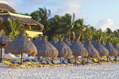 De lanterfanters van de zon en parasols op een tropisch strand Royalty-vrije Stock Afbeeldingen