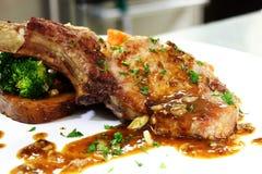 De lapjes vlees van het varkensvlees met saus die met peterselie wordt verfraaid Royalty-vrije Stock Afbeelding