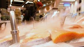 De lapjes vlees van rode vissen liggen braakakker in het ijs in een supermarktvitrine Op de achtergrond, kiezen de kopers product