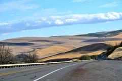 De largo y carretera con curvas a través de la Rolling Hills de Oregon central Imágenes de archivo libres de regalías