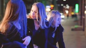 De las muchachas que camina de la noche ventana de la tienda de la calle de la diversión hacia fuera almacen de video