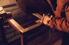 De lasser in een beschermend masker in een donkere winkelvloer trof om aan metaal te werken voorbereidingen Stock Foto