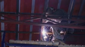 De lasser last metaalbouw in de grote hangaar stock video