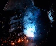 De lasser last metaaldelen, vele vonken en dampen, lassen, lassenboog, heldere flits, close-up, fabriek stock foto's