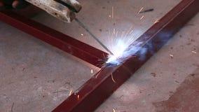 De lasser op het werk in de metaalindustrie en bouwt structuur stock videobeelden