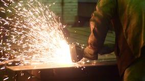 De lasser werkt cirkelzaag, snijdt metaal Vliegen van vonk van heet metaal in langzame motie stock video