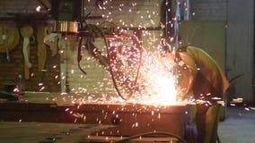 De lasser werkt cirkelzaag, snijdt metaal Vliegen van vonk van heet metaal in langzame motie stock videobeelden