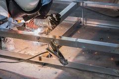 De lasser in werkt, het u-Staal van het Werknemerslassen gebruikend lassersmachine stock afbeelding