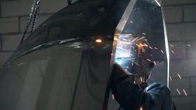 De lassersarbeider in overall en in een lassenmasker last de roestvrije grote ton of de pool van het staalbad stock video