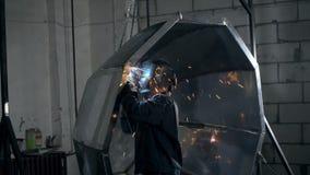 De lassersarbeider in overall en in een lassenmasker last de roestvrije grote ton of de pool van het staalbad stock footage