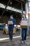 De leden en de vrijwilligers van BookCycle het UK dragen vakjes van boeken Royalty-vrije Stock Afbeeldingen
