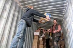 De leden en de vrijwilligers van BookCycle het UK laden een container Stock Afbeeldingen