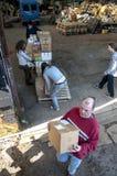 De leden en de vrijwilligers van BookCycle het UK laden een container Stock Foto