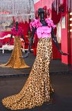 De ledenpoppen die zich in lange lijn langs de straatmarkt bevinden die de kleurrijke Luipaard van de doekenvrouw dragen kleurden stock afbeelding