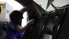 De leerling Mechanisch Working On Car verwijdert de veiligheidsgordel stock videobeelden