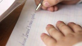 De leerling op de school schreef op een stuk van notadocument, close-up stock video