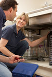 De Leerling van het Onderwijs van de loodgieter om de Gootsteen van de Keuken te bevestigen Royalty-vrije Stock Afbeelding