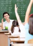 De leerlingen zetten hun handen tot antwoord Stock Foto