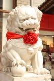 De leeuw van de steen met een rode boog in een straat van Peking royalty-vrije stock foto's