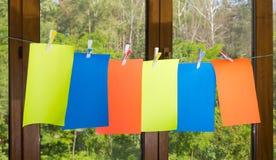 De lege bladen van gekleurd document, maken wasknijpers op clothesli vast Stock Foto